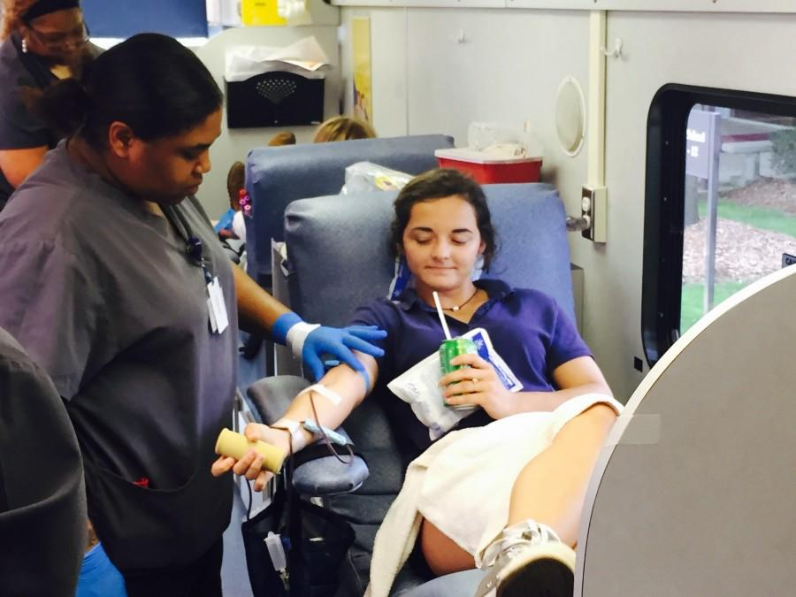 Tori Jones sips on a sugary drink as she donates blood