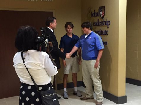 Cameras roll as GLI director Col. William Merrill congratulates juniors Tanner McCraney and Kole Crotwell on their contribution to the Red Cross. Photo courtesy of Jackson Prep.