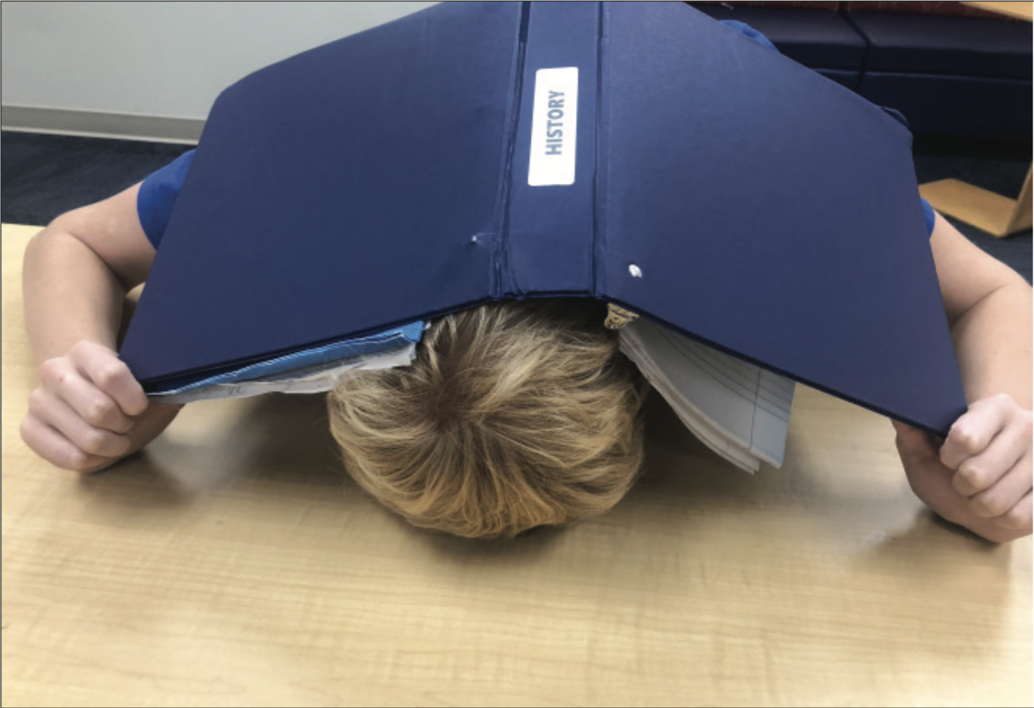 Sophomore Camp Carter falls to the pressure of exams, holding his history binder over his head in defeat.
