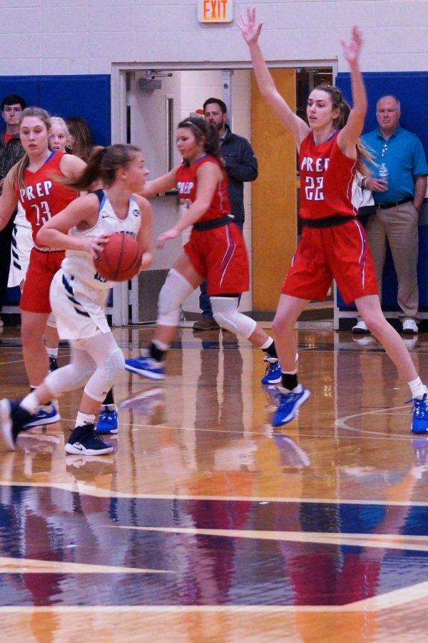 Julia Zouboukos, Mackenzie Shoemaker, and Caroline Dreher play defense.