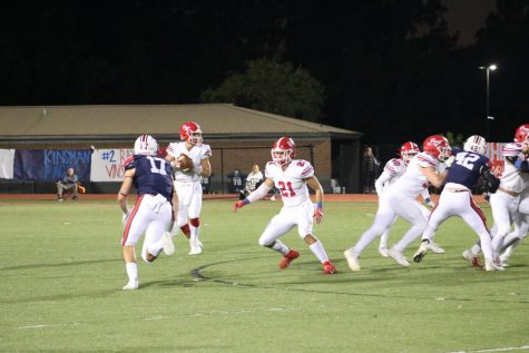 Riley Maddox drops back to pass as John Kennedy Nowell keeps the pocket clear. Photo by Lily Flowers