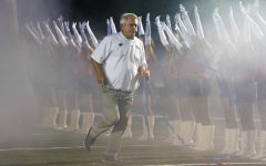 Coach Black jogs to the sideline behind his players. Photo courtesy of Reed Hogan.