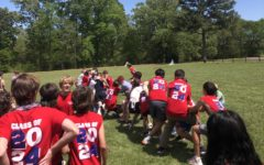 Students engage in a tug-of-war on a beautiful day at the ninth grade retreat.